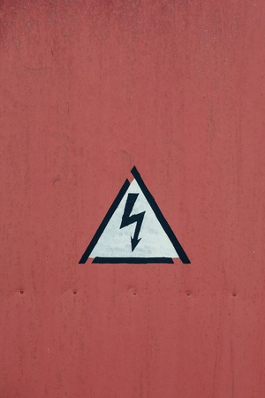 Vintage Metal Sign -  Danger High Voltage on the door, A fragment of an old red iron door, the Soviet Russian Industrial factory, closeup Stock Photo