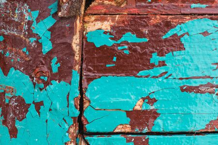 texture Close Up of Chipped colorful peeling paint, covered with crumbling Paint on an Exterior wood door , outdoor Stock Photo