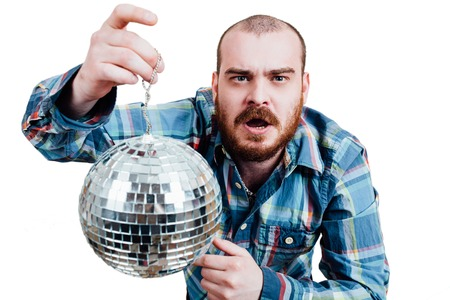 interrogative: Portrait of a red-bearded, balding male brutal. White isolated background. A man in a blue plaid shirt, holding disco ball in hand. It shows a finger. Open mouth.  Interrogative looking at the camera Foto de archivo