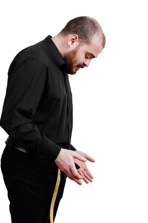 impotence: Portrait of a red-bearded, balding man. Unbuckling belt. Question of impotence or sexual organ size .Peny and medical or psychological problem. Erectile dysfunction. looking down. He spreads his hands
