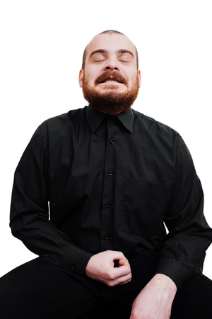 Portrait of a red-bearded, balding male brutal. White isolated background. He is sitting on a chair. looking at the camera. Masturbation humor, hand. with clenched teeth. Eyes closed