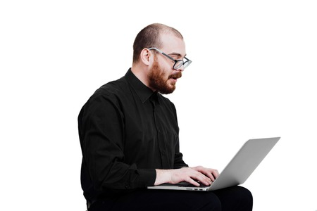 Portrait of a red-bearded, balding male brutal. White isolated. Man in a black shirt pants.  Sitting with laptop had the idea.  Grandmas glasses. diopter Geek . Looking at the computer. Side view .