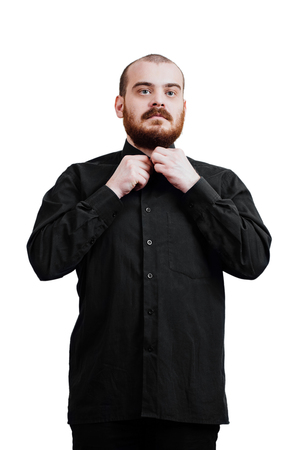 fastened: Portrait of a red-bearded, balding male brutal. White isolated background. Black shirt and pants. Fastened the top button.