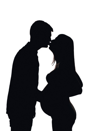 Young pregnant couple expecting. silhouette, white isolated. Pregnancy.  Kiss holding hands