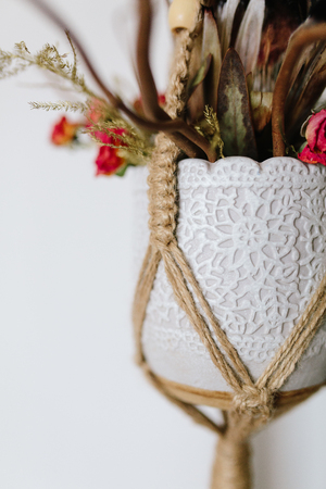 Bouquet in a vase jewelry Knitted macrame terrarium holder . On a white background, closeup