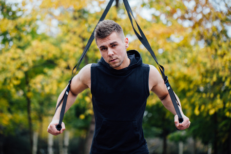 TRX training. Man Instructor at the park doing TRX Excersise. Fitness man workout. Fitness style. Sport and fitness.