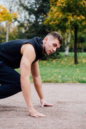Fitness man training and jogging in fall park. Ready to start. Healthy lifestyle and sport concept