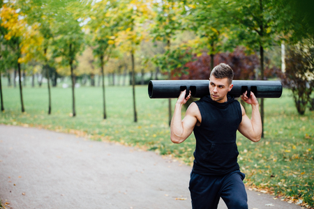 Male fitness doing exercise lunge with vipr, morning workout in the park. Fall alley. Stock Photo