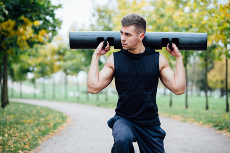 lunge: Male fitness doing exercise lunge with vipr, morning workout in the park. Fall alley. Stock Photo
