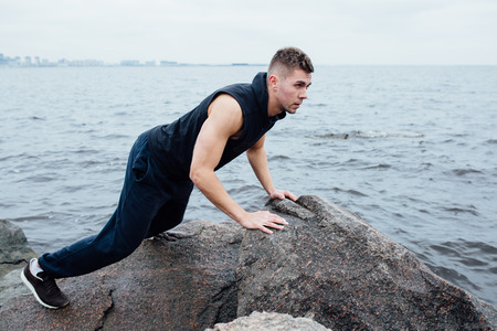 acts: Strong man acts yoga on the rocks beach in the morning against sea. static model posing