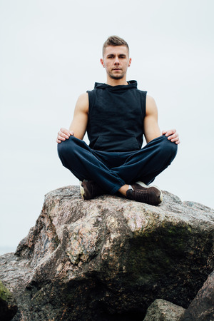 Strong fitness yoga man in lotus pose on the rock beach near the ocean. Harmonic concept, peace and success