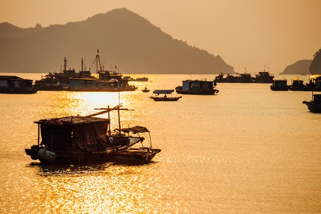 Asian fishing boats at sunset on a background of mountains. Stock Photo