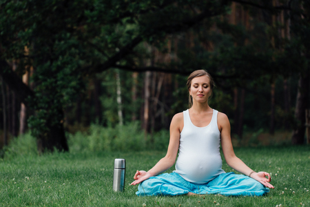 pregnant yoga in the lotus position. in the park on the grass , outdoor, health woman, female. Stock Photo