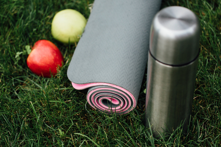 Close-up of attractive gray-pink rolled yoga or fitness mat with apples  at park on a grass .