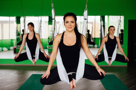 young women making antigravity yoga exercises with a group of people. aero fly fitness trainer workout. white hammocks.