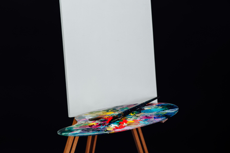 canvas background: Tools of the artist. Brushes, wooden easel tripod, palette colorful. Black background, studio, nobody.