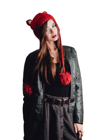 Pretty young woman wearing a hand knitted red hat on white background. Isolated. Beautiful girl in with Ear flap.