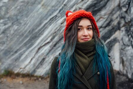 Portrait of a beautiful hipster girl on the background  the rocky cliffs. Dyed hair, blue, long.