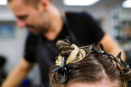 young model with colored topknot and hidden undercut bleached hair Stock Photo