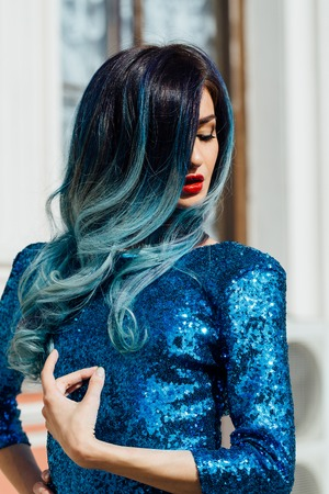 Fashion portrait of gorgeous girl with blue dyed hair long. The beautiful evening cocktail dress.