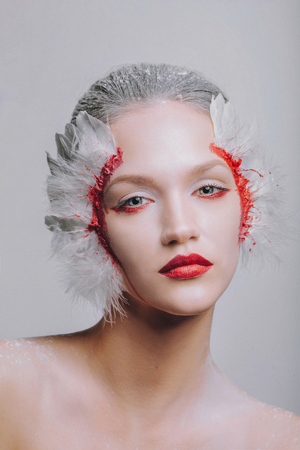 Fashion close-up portrait of a model girl swan with a beauty amazing make-up. Perfect skin, feathers in the blood, fairy-tale image of a ballerina fallen angel. White background silver hair. Halloween