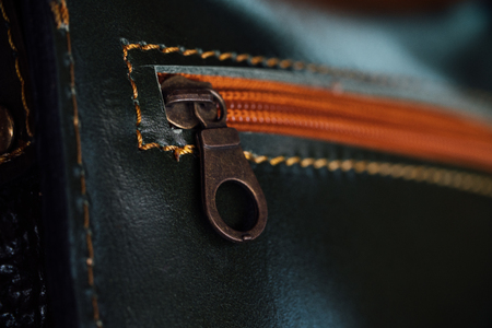 Womens black purse with orange zipper close-up, stitch.Macro fragment of a leather bag or purse.
