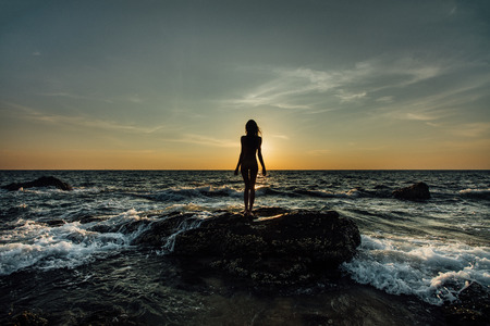 Silhouette of a beautiful girl at sunset by the sea, on a sea stone in a swimsuit. Waves, foam.