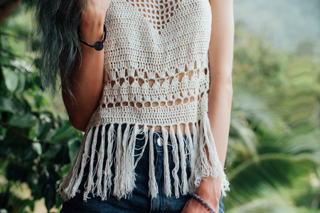 Girl in white knitted blouse against the background of the jungle. Jackets shorts.