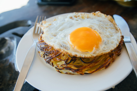 Potato pancakes with fried eggs are served with a knife and fork. On the oak table. Cafe by the sea.