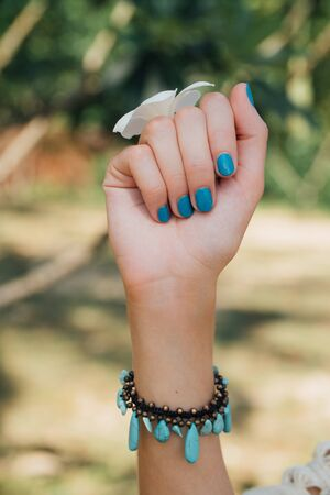 subtropical plants: White plumeria Flower on hand With a turquoise bracelet .