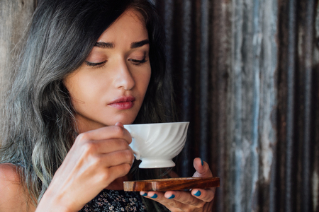 Portrait of a girl drinking coffee in a vintage cafe on the terrace in Asia. Sniffs, drinks.