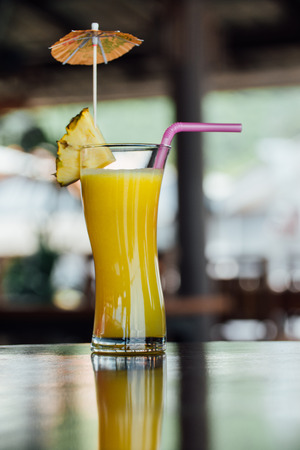 Refreshing pineapple cocktail glass with slices of pineapple, pink juice straws and decoration