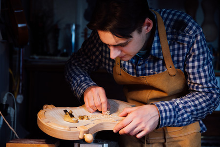 Master artisan luthier working on the creation of a violin. painstaking detailed work on wood. Zdjęcie Seryjne