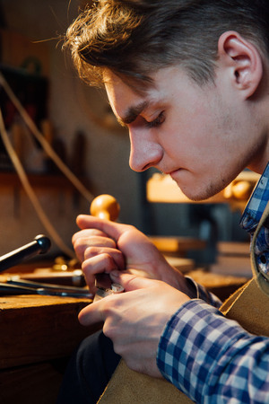 sound box: Master artisan luthier working on the creation of a violin. painstaking detailed work on wood. Stock Photo
