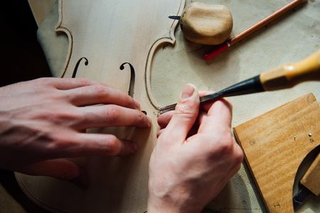 Master artisan luthier working on the creation of a violin. painstaking detailed work on wood. Stock Photo