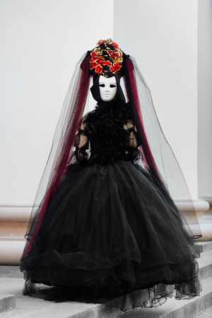 Witch portrait in black vintage dress, White mask covers face. Woman widow halloween.