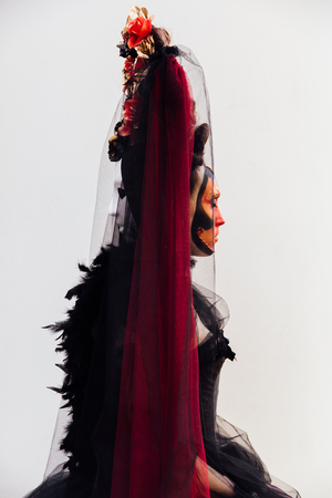 Two-faced woman portrait in black vintage dress. Witch woman widow with red art make-up .