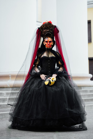 Witch portrait in black vintage dress. Woman widow with red art make-up for halloween. Stok Fotoğraf