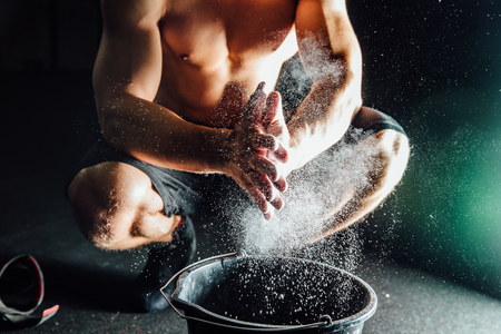 magnesia: Fitness model trainer rubs his hands with chalk and talc so that fingers do not slip or slide.