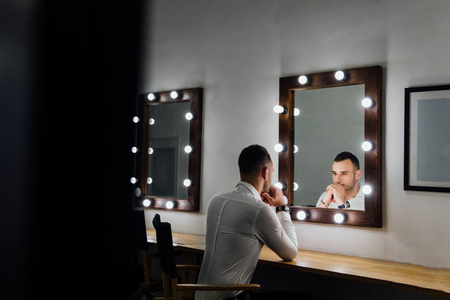 Portrait of handsome young man in white shirt looking into the mirror. Stock Photo - 83017246