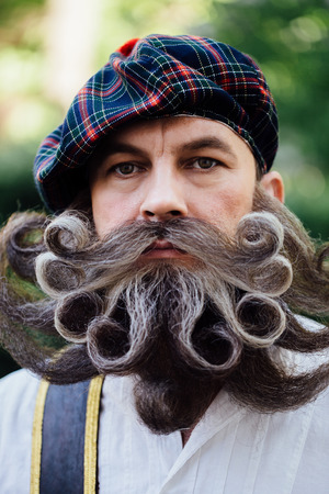 Handsome portrait of a brave Scot with a amazing beard and mustache curls in the Hungarian style. Stock Photo