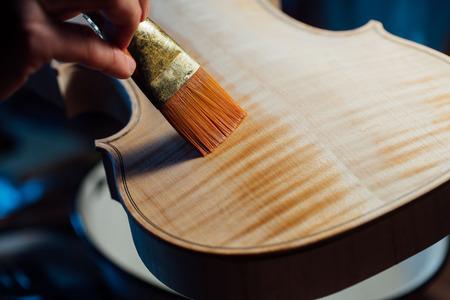 varnished: violin maker varnishing a violin body close up.