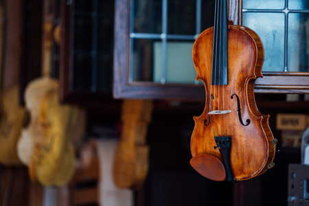 Closeup view of beautiful brown wooden string musical instrument of violin.