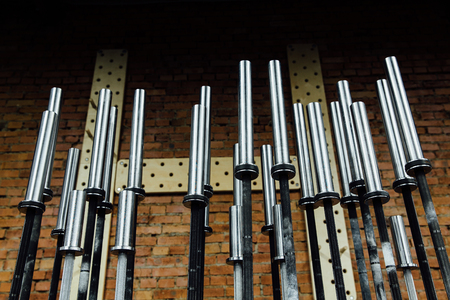 rack of chromed vertical dumbbells on the PEGBOARD wall background and Benches around.