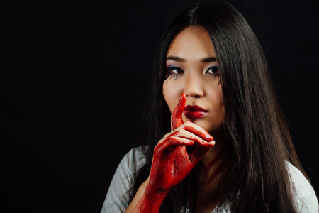 close-up portrait of a young, beautiful Asian girl on Halloween. woman covering her face bloody hand.