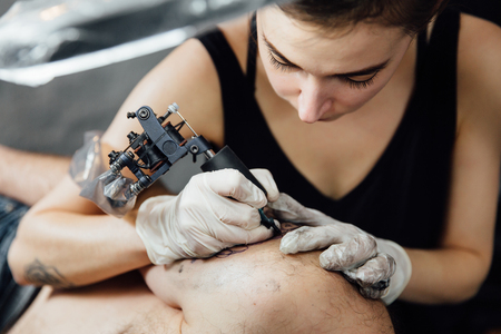 close portrait of girl tattoo master in process of making tattoo with machine on client man shoulder Stock Photo
