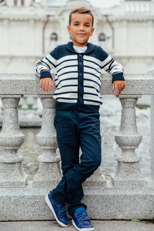Stylish little boy in sunglasses and fashionable clothes . Childrens fashion