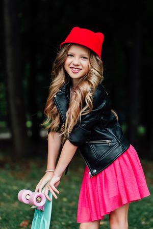 Portrait stylish fashion little girl child posing with skateboard on city park.