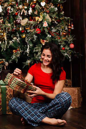 Woman with christmas present box on background decorated christmas tree. Brunette in a red shirt.
