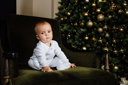 little kid sits on a green chair in white sliders against the Christmas tree.